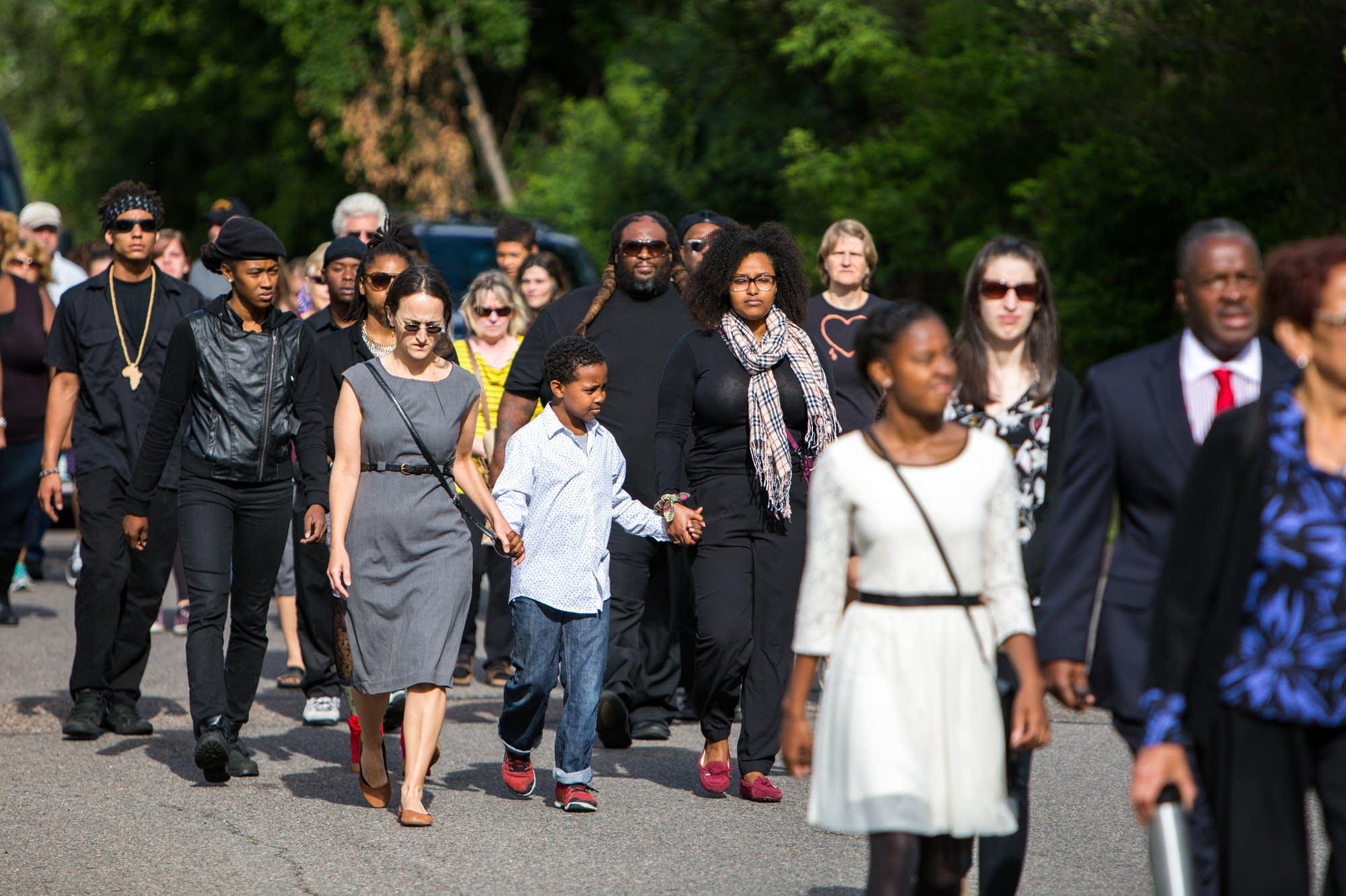 Mourners walk down Concordia Avenue