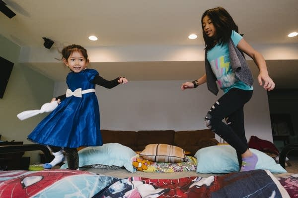 Leala and Alexis jump on a bed together.