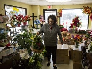 Patti Thomas prepares a flower basket for an order at her floral shop.