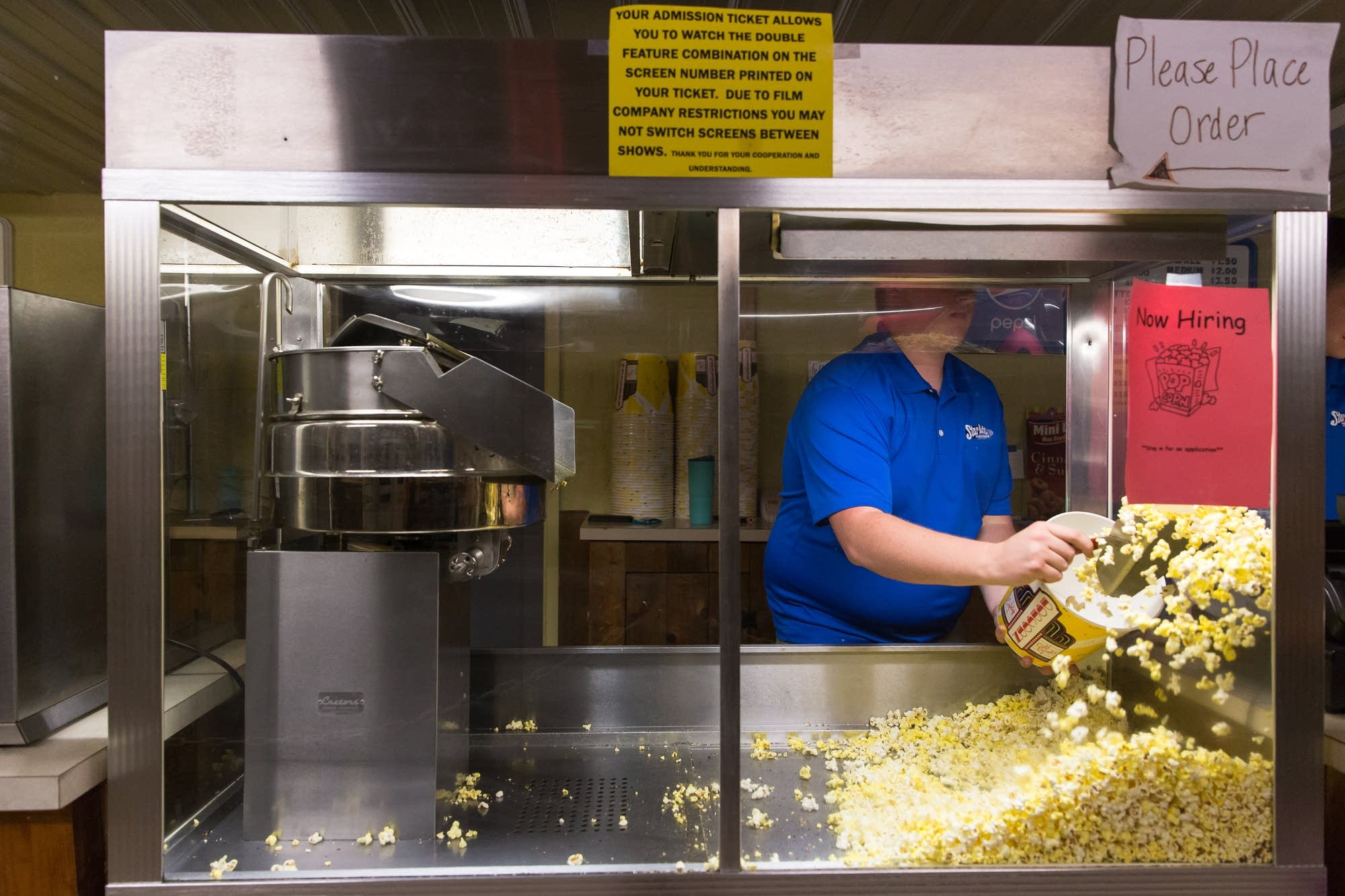 18-year-old Henry Fitzsimmons scoops popcorn for a customer.