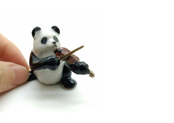 A figurine of a panda playing the violin