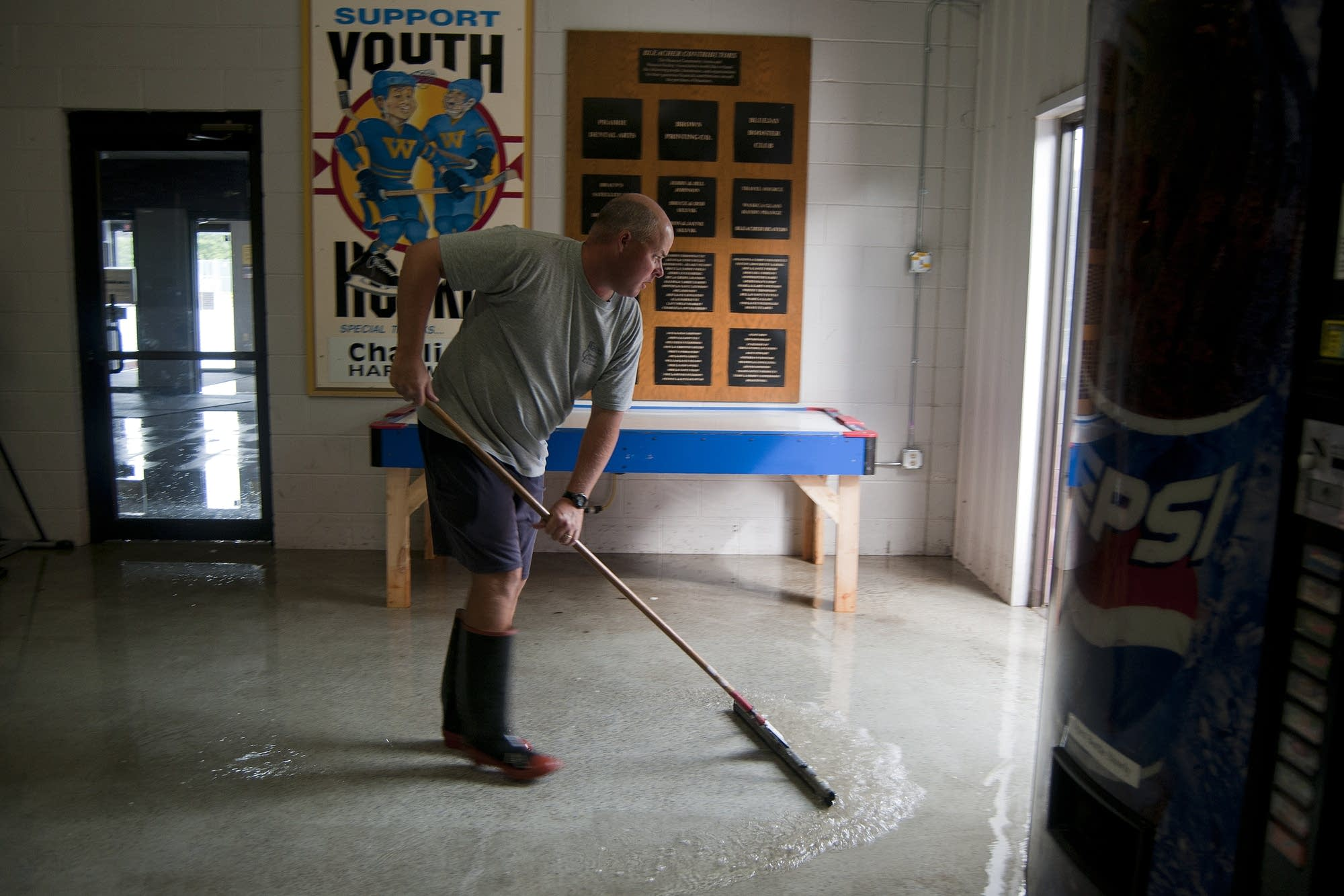 Kyle Collins sweeps water out of the hockey rink.