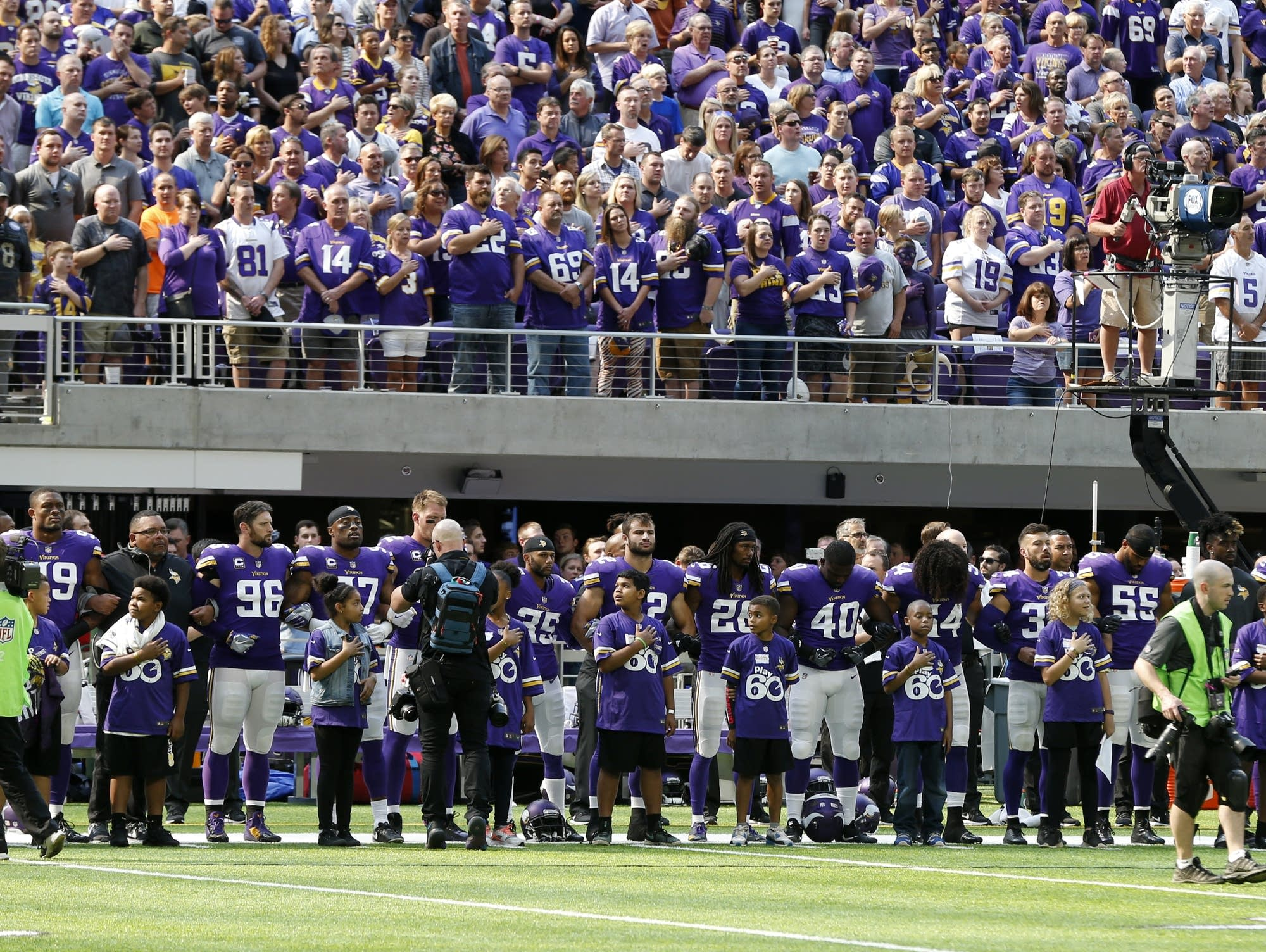 Minnesota Vikings players lock arms during the national anthem