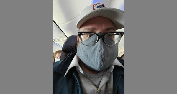 Andrew selfie  on airplane w/ gray mask and beige ballcap