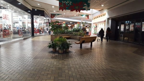 Interior of a shopping mall, 1990s era style, w/ benches and brick planters