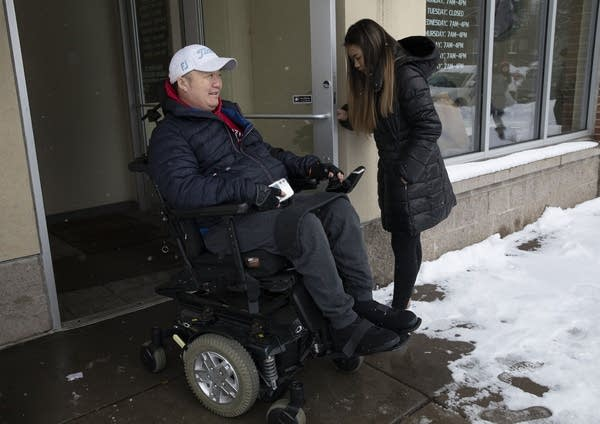 A teen holds a door open for a man in a wheelchair.