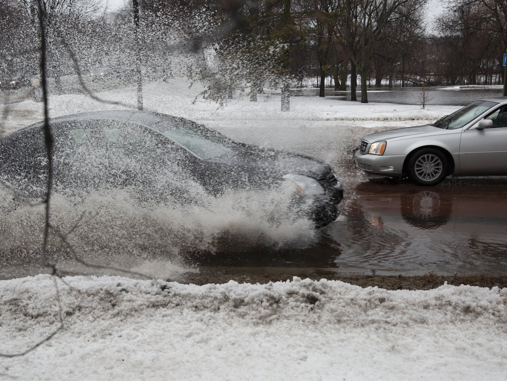 A car drives through water pooled on Minnehaha Parkway and Cedar Avenue