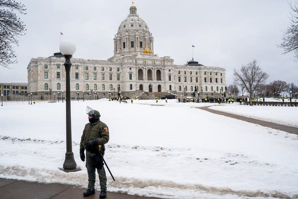Police in riot gear stand at the capitol.