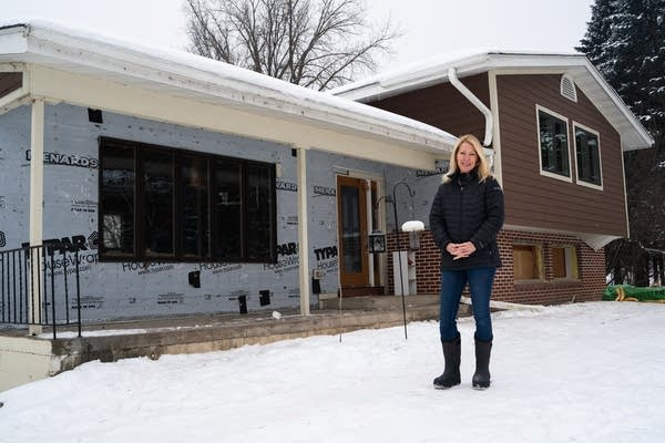 A woman stands in front of a house with some of the siding ripped off.