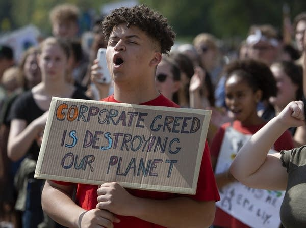"""A teen holds a sign that reads """"Corporate green is destroying our planet."""""""