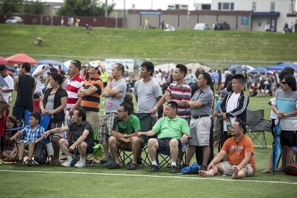 Spectators follow a soccer game.