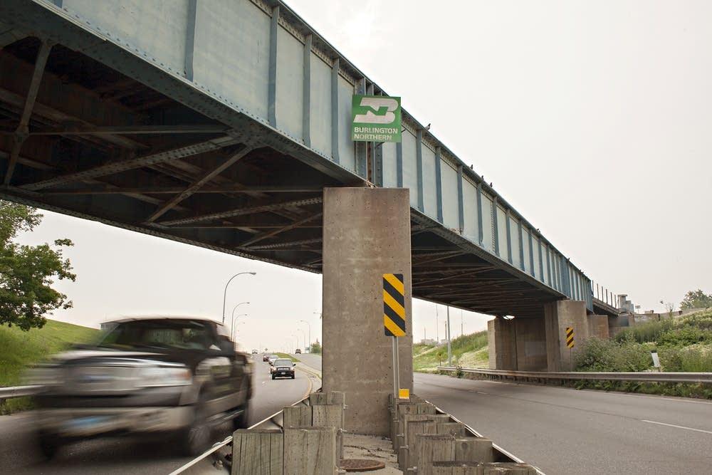 Traffic passes under a railroad bridge