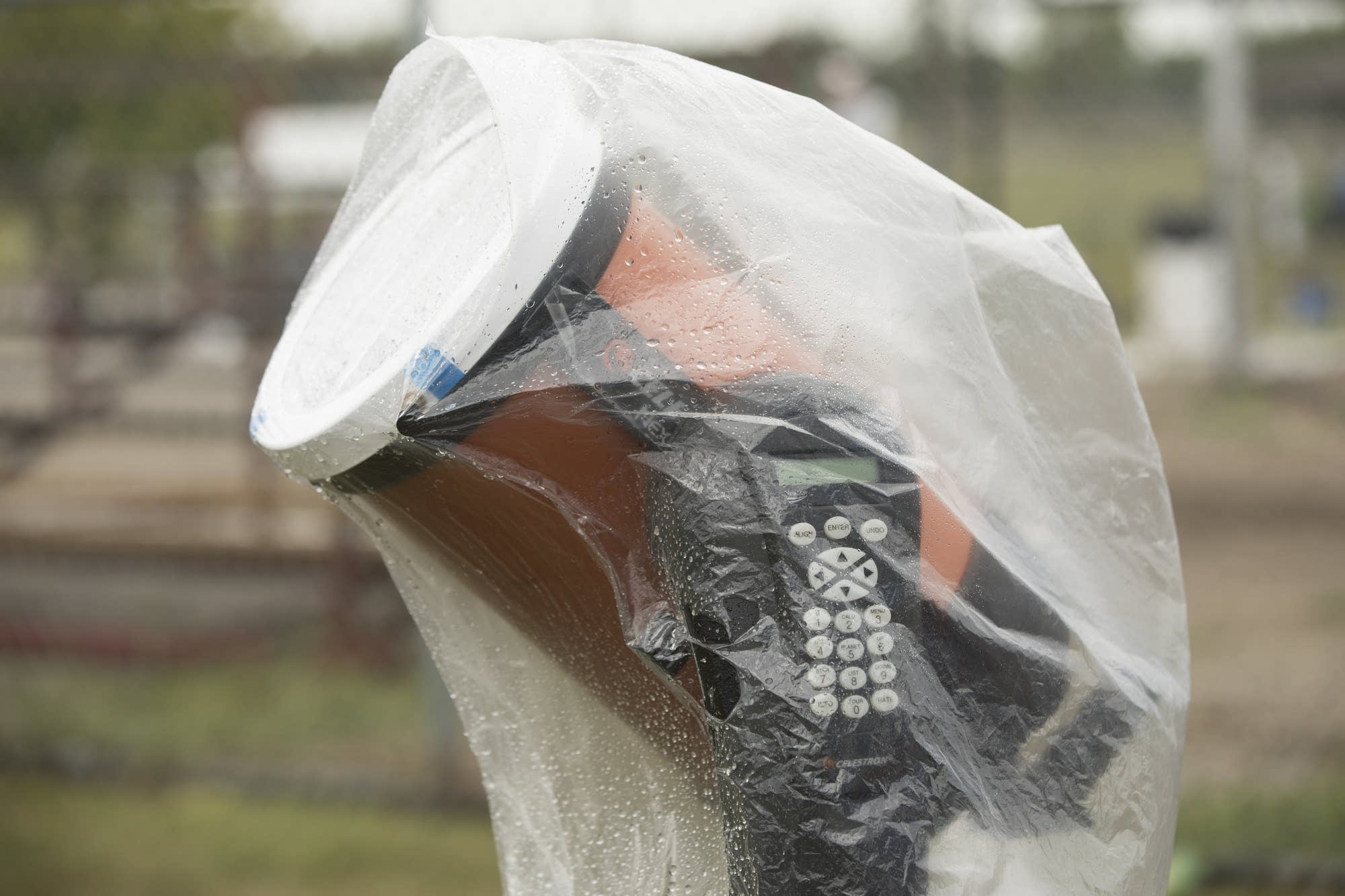 An astronomer put a plastic bag over his telescope to keep it dry.