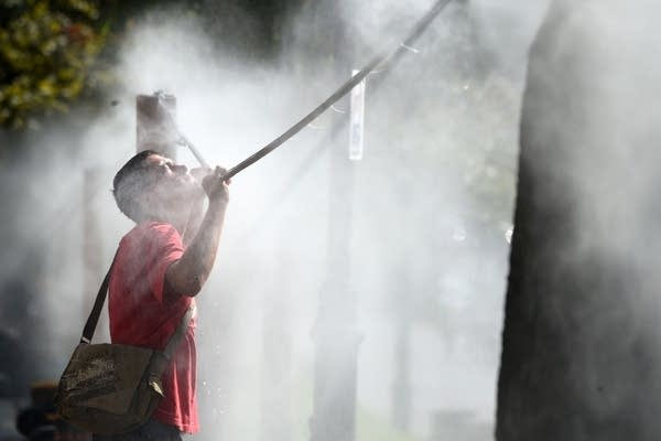 A man cools off with water spray.