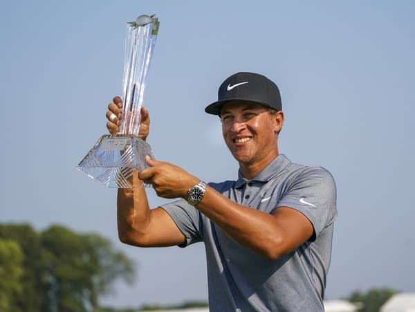 A golfer holds up a trophy