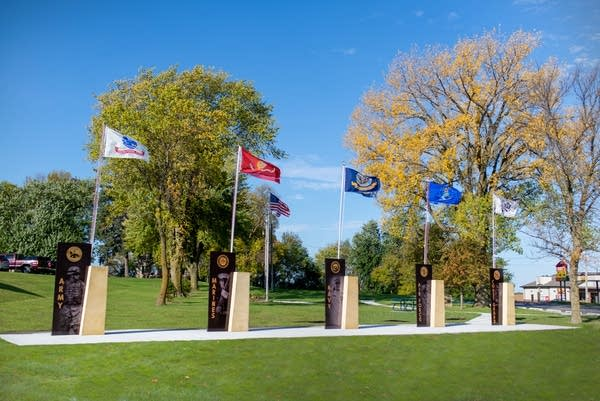 A row of flags attached to monuments on a sunny day.