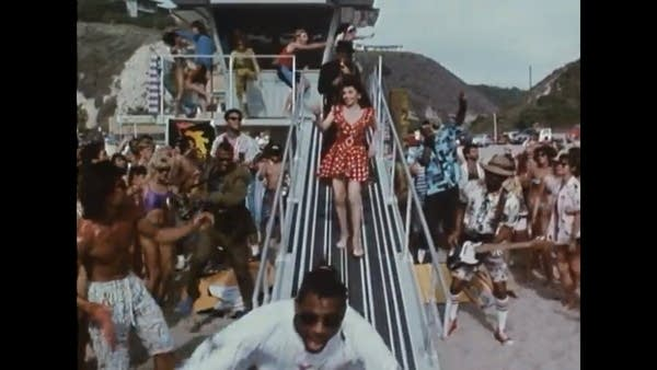 Actress Annette Funicello partying on a beach in a red dress w/ many people
