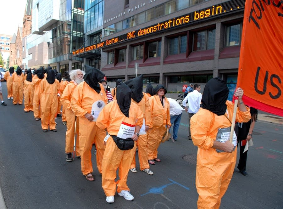 Protesters march in orange jumpsuits