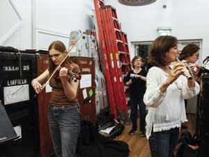 Fantasy campers tune their instruments before rehearsal.