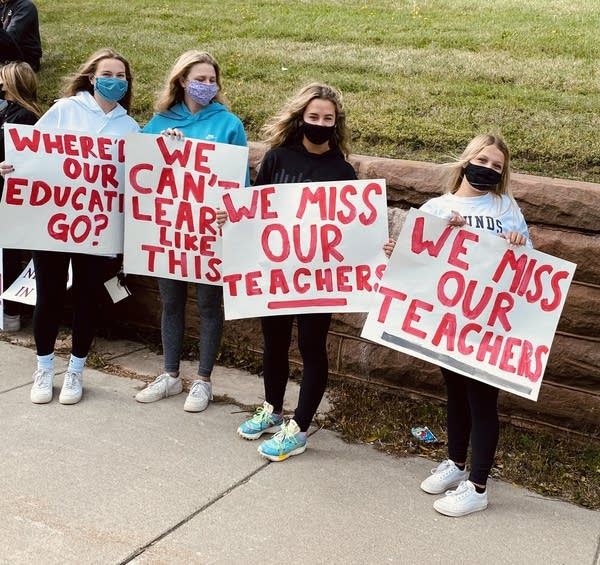 """Four teenagers hold signs that read """"We miss our teachers."""""""