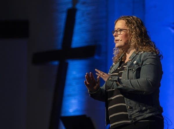 A woman speaks on stage near a cross.