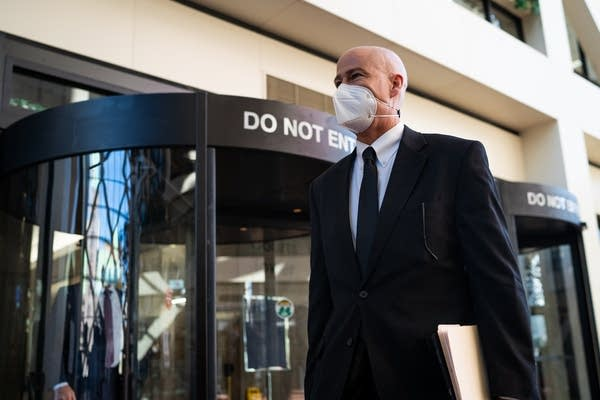 A man with a mask walks in front of revolving doors.