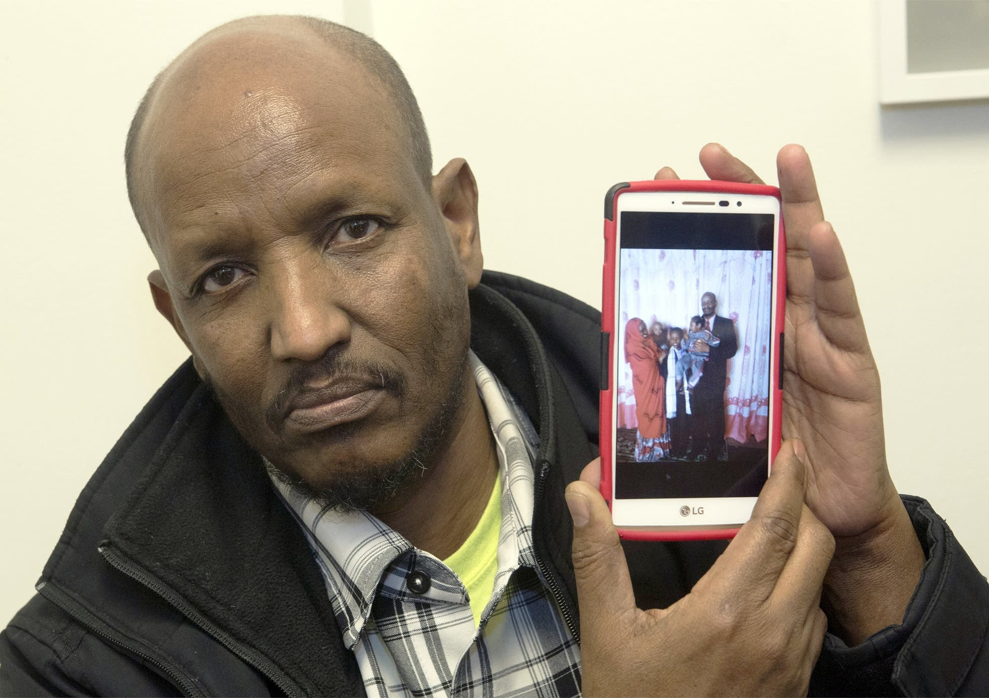 Mahamed Iye shows a photo of his wife and two children.