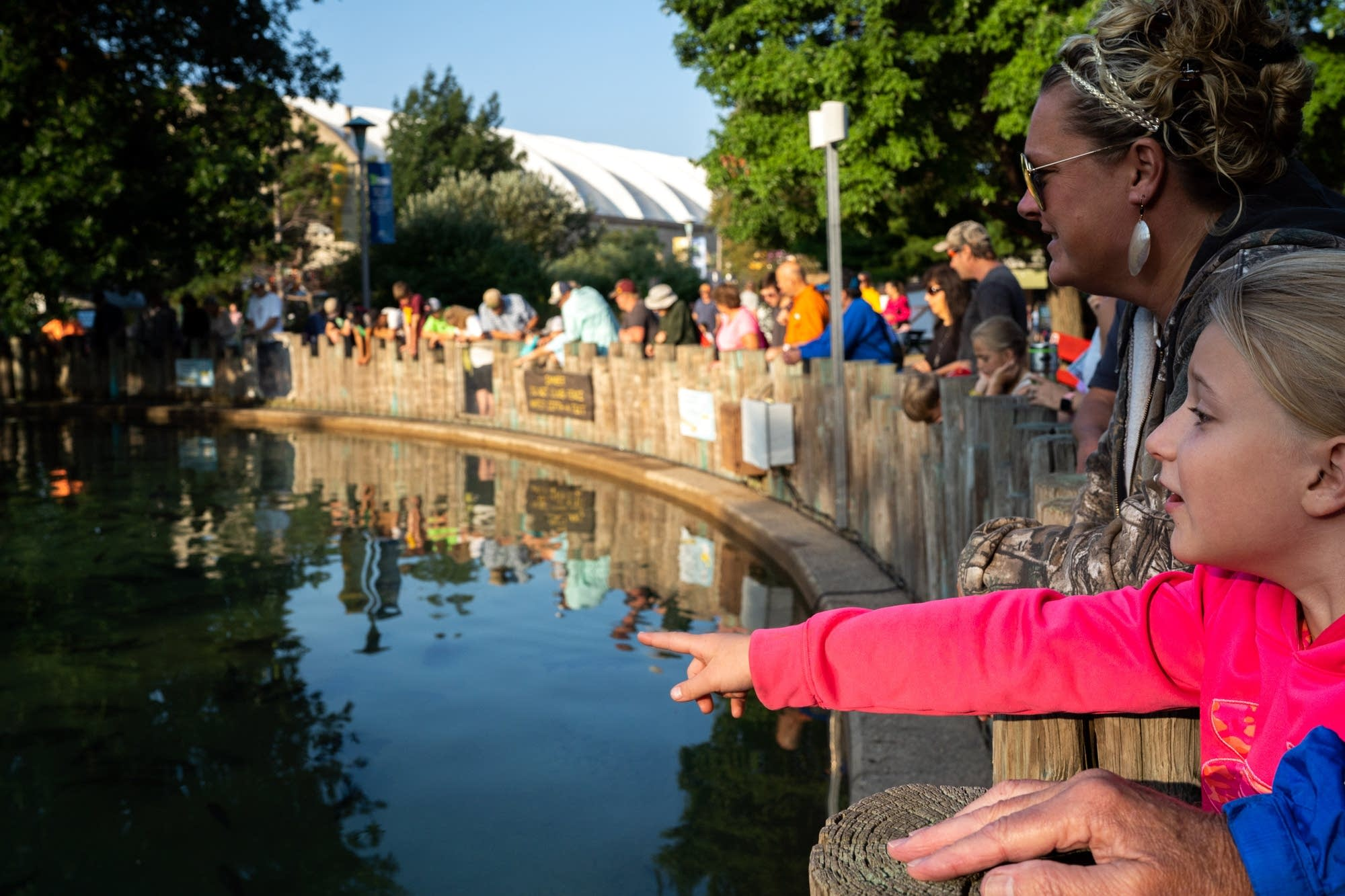 Eight-year-old Anna Weber points out a large fish in the DNR Fish Pond.