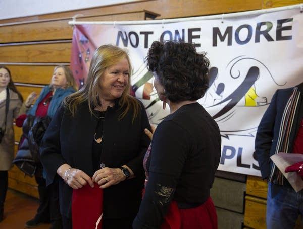 Two women speak in a gymnasium.