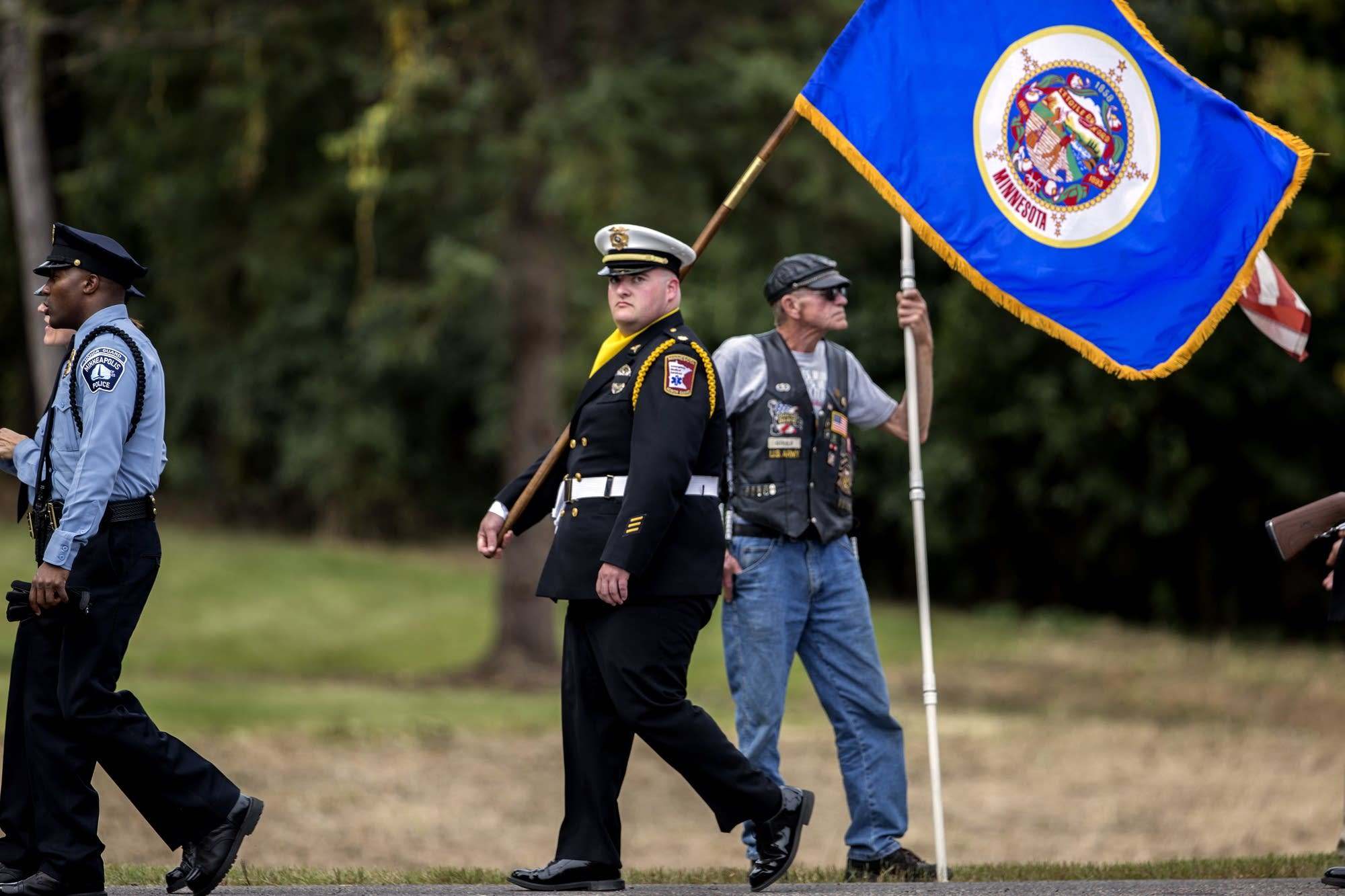 A member of the Minnesota Honor Guard carries the state flag.