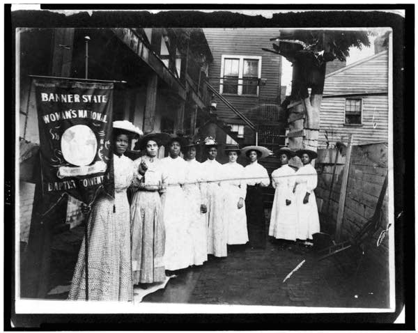 Nine African American women are standing, with a banner.