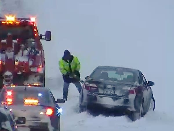 A tow truck operator works to remove a car that went off the road