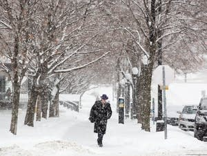 A man walks down the sidewalk in heavy snow.