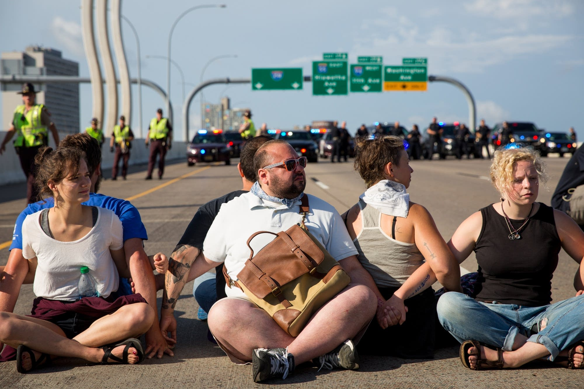 Protesters take a seat before being arrested.