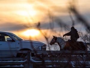 A man rides his horse across a bridge.
