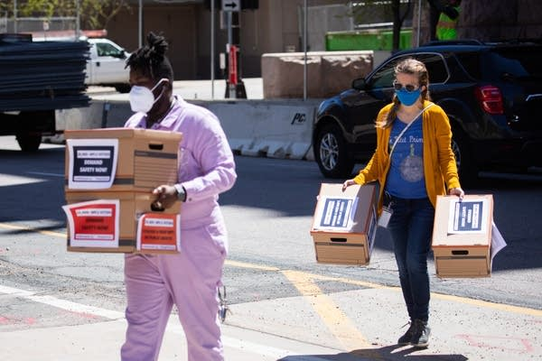 People carry boxes across a street.