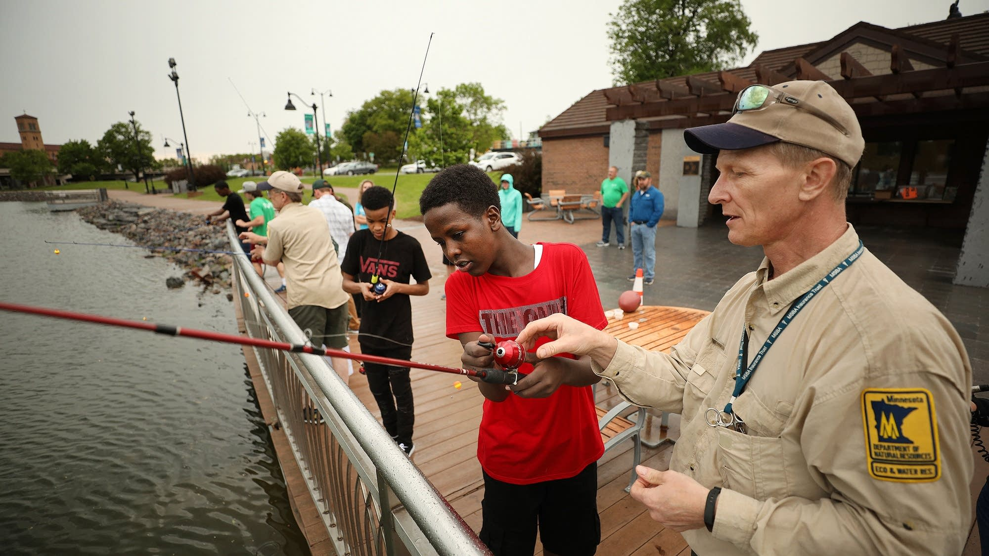 Mark Hauck of the Minnesota DNR helps Yusuf Ahmed use the rod and reel.