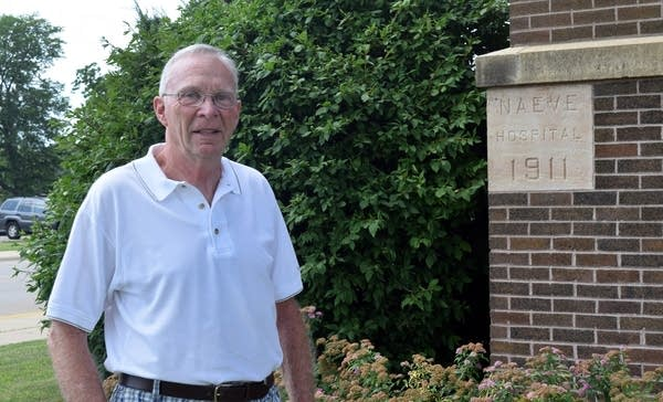 Retired Dr. William Buege stands in front of the Albert Lea Hospital.