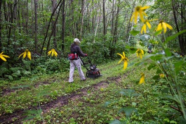 Karen Stenberg pushes a mower down the trail