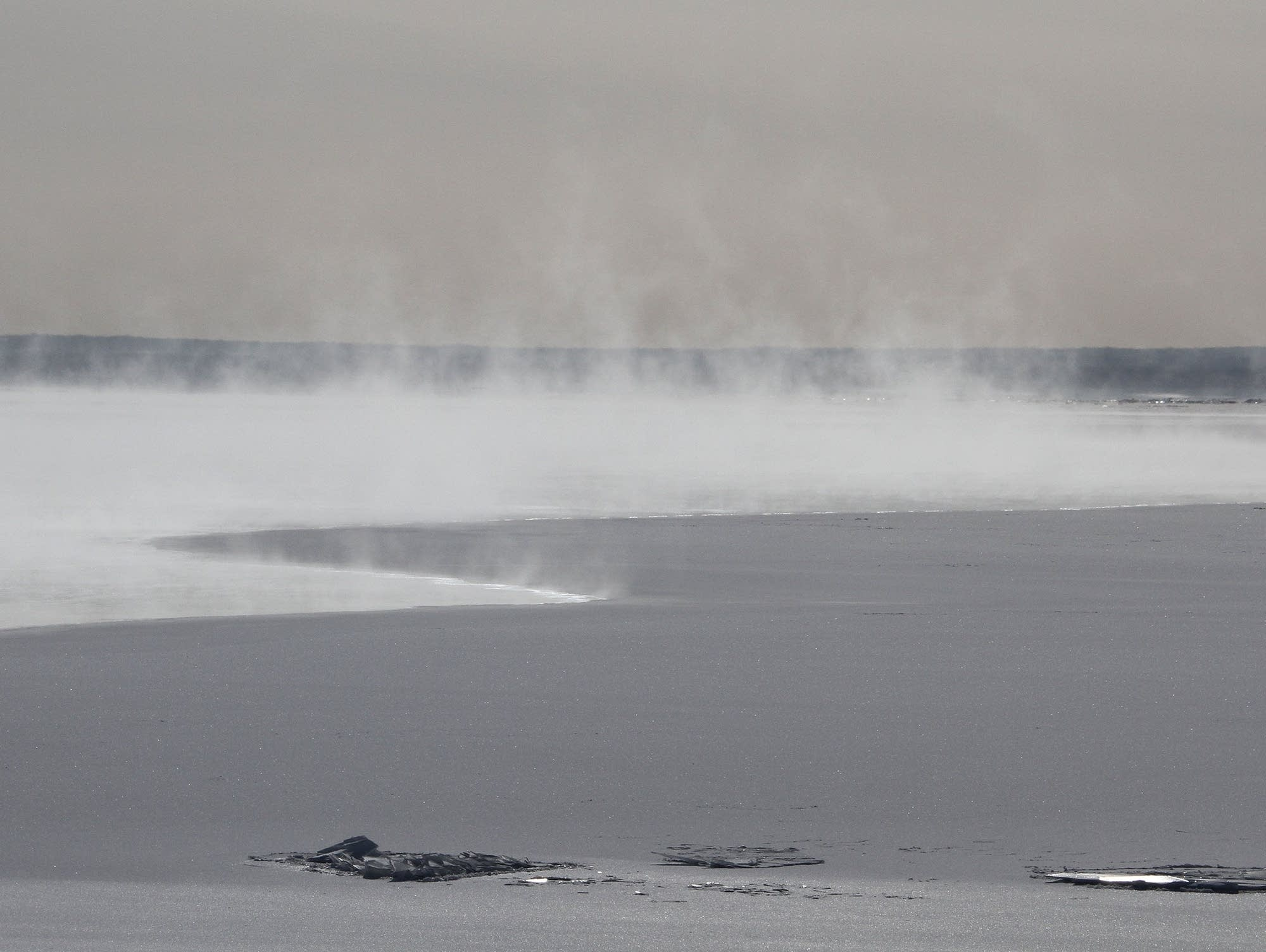 Sea smoke rises from patches of open water on Lake Superior