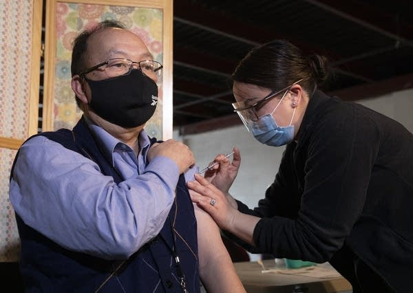 A man holds his shirt as he receives a vaccine.