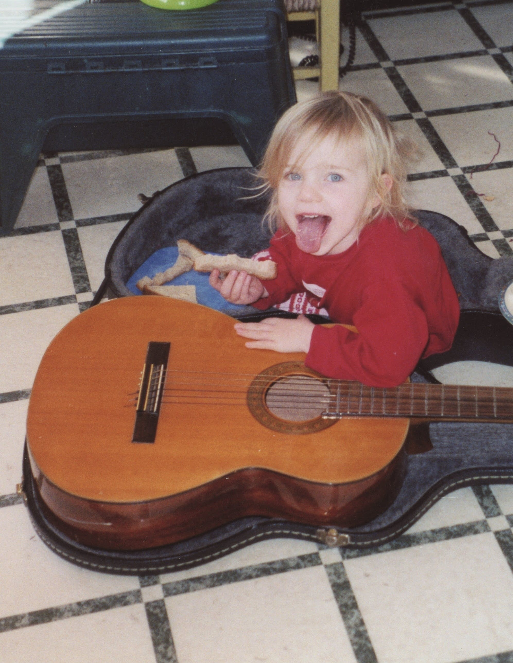 Young child sitting with guitar in case.