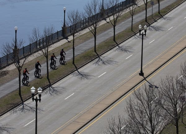 Four bicyclists on a path beside a quiet road.
