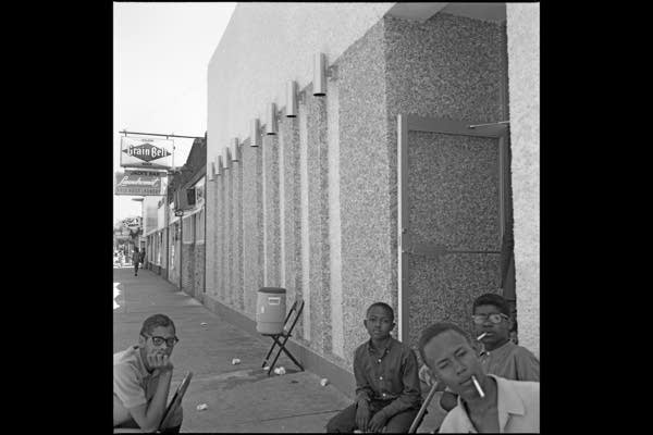 Four young men sit in front of a building with cigarettes in their mouths.