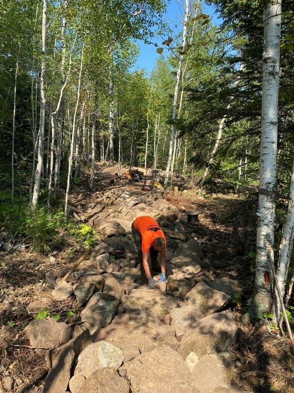A builder places a rock on a bike trail.