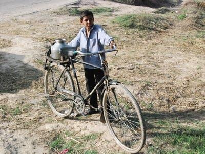 45b0ac 20160520 a boy in ranila totes water on a bike