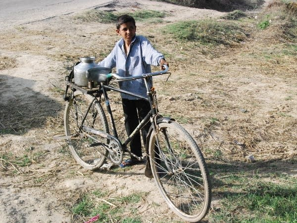 A boy in Ranila totes water on a bike