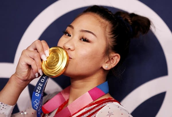A woman kisses her Olympic gold medal.