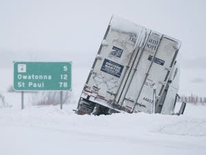 A tractor-trailer is stuck in the snow on the side of Interstate 35.