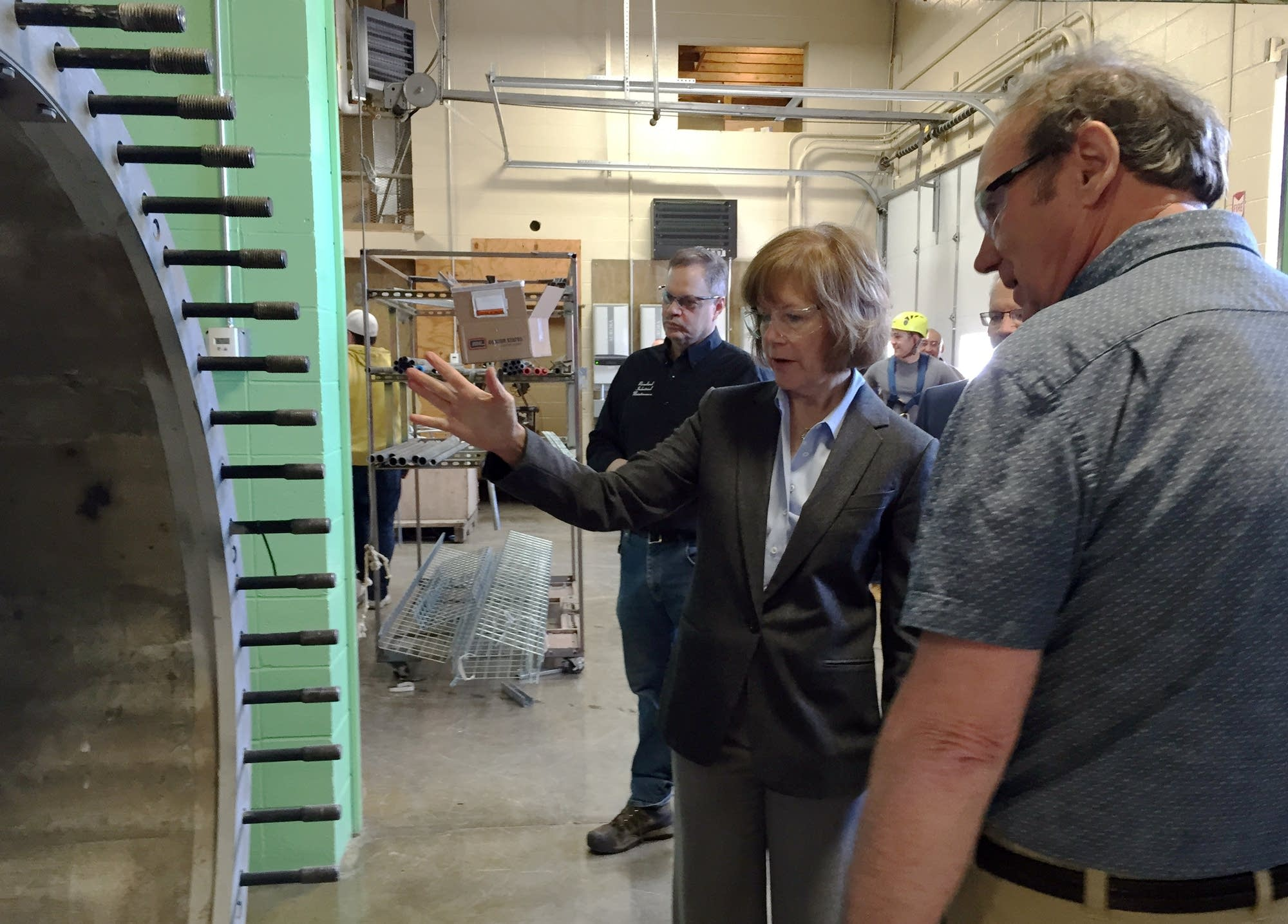 Then-Lt. Gov. Tina Smith looks at a wind turbine base with Steve Vietor.